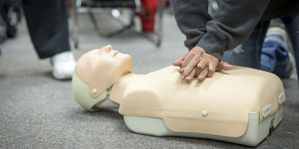 Man giving CPR to a dummy